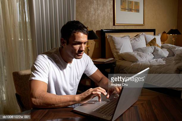 Man using laptop in bedroom