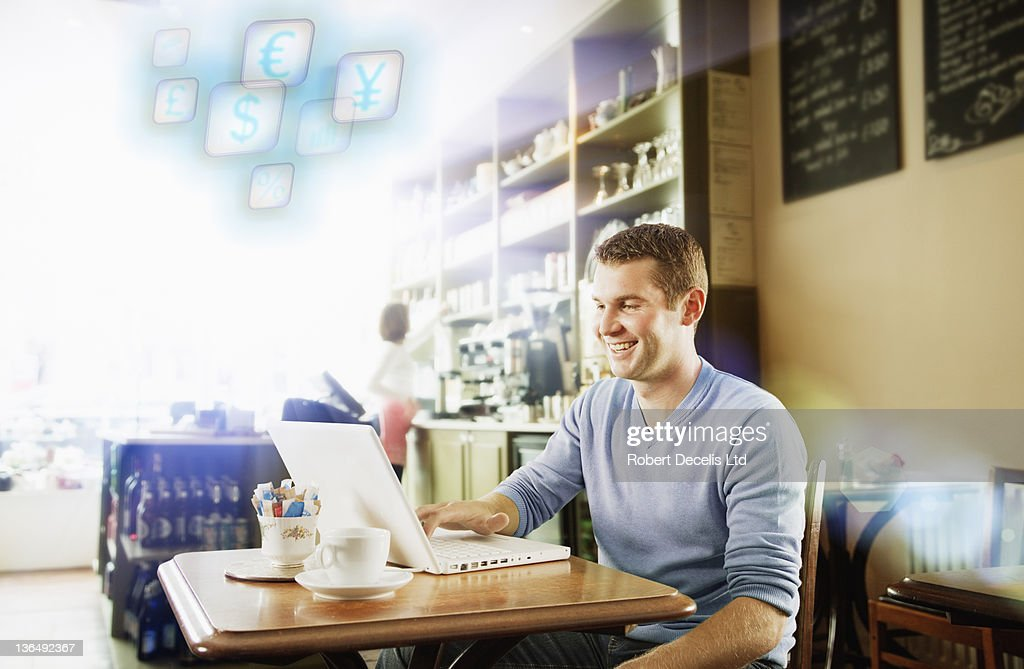 Man using laptop in cafe : Stock Photo