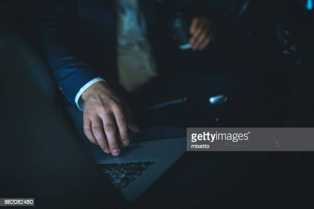 Man using laptop in car for cyber criminal