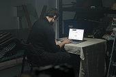 Man using laptop in a dark room.
