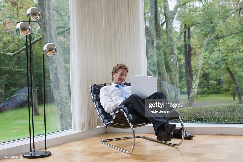 Man Using Laptop in Designer Chair in Modern House