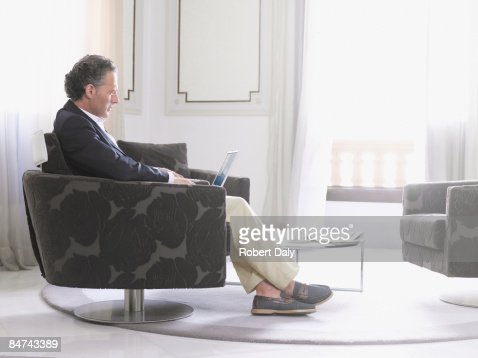 Man using laptop in modern hotel suite
