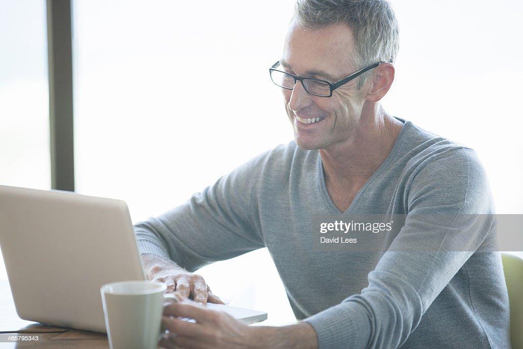 Man using laptop indoors : Stock Photo