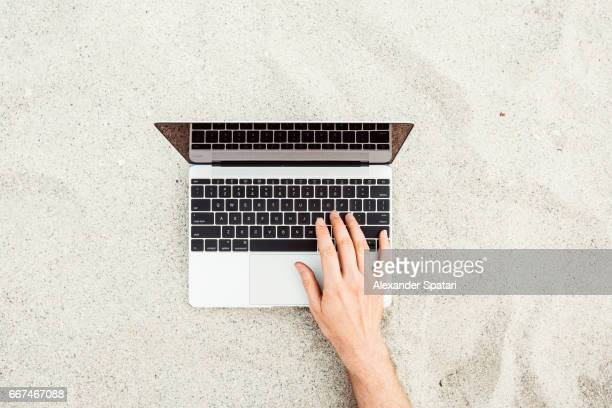 Man using laptop on a sandy beach, high angle view