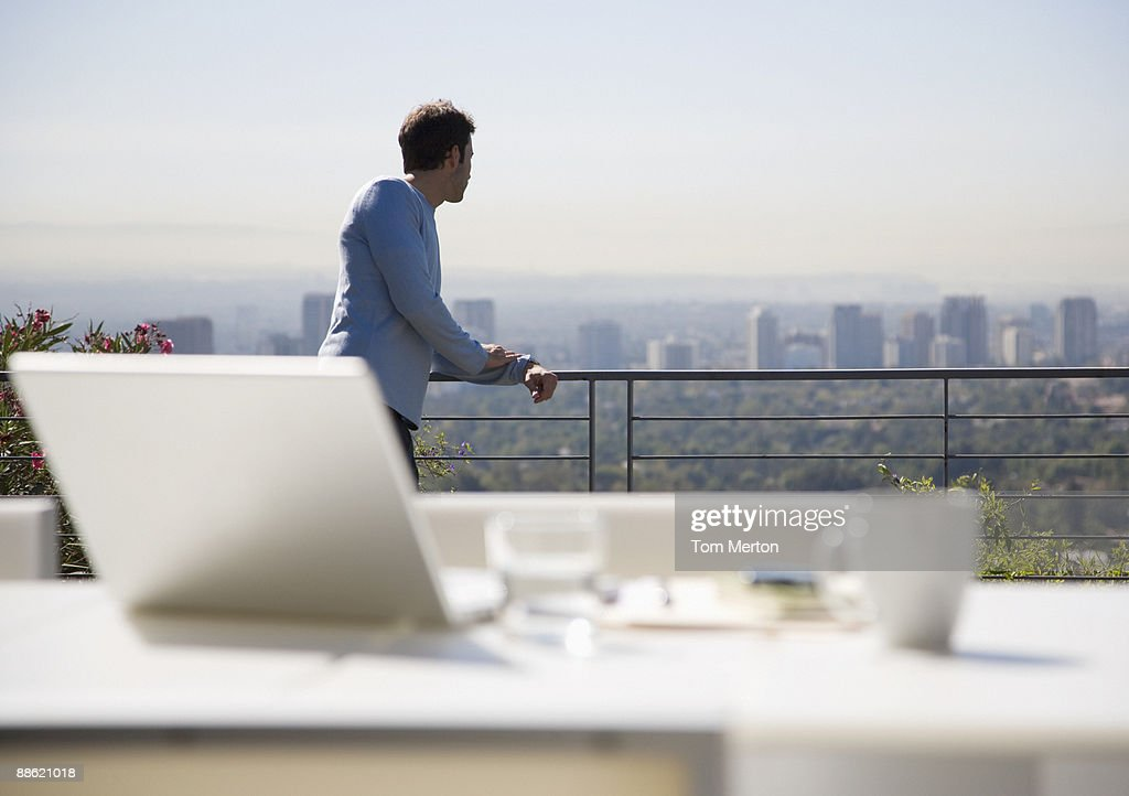 Man using laptop on balcony overlooking city : Stock Photo