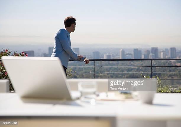 Mann mit laptop auf Balkon mit Blick auf die Stadt