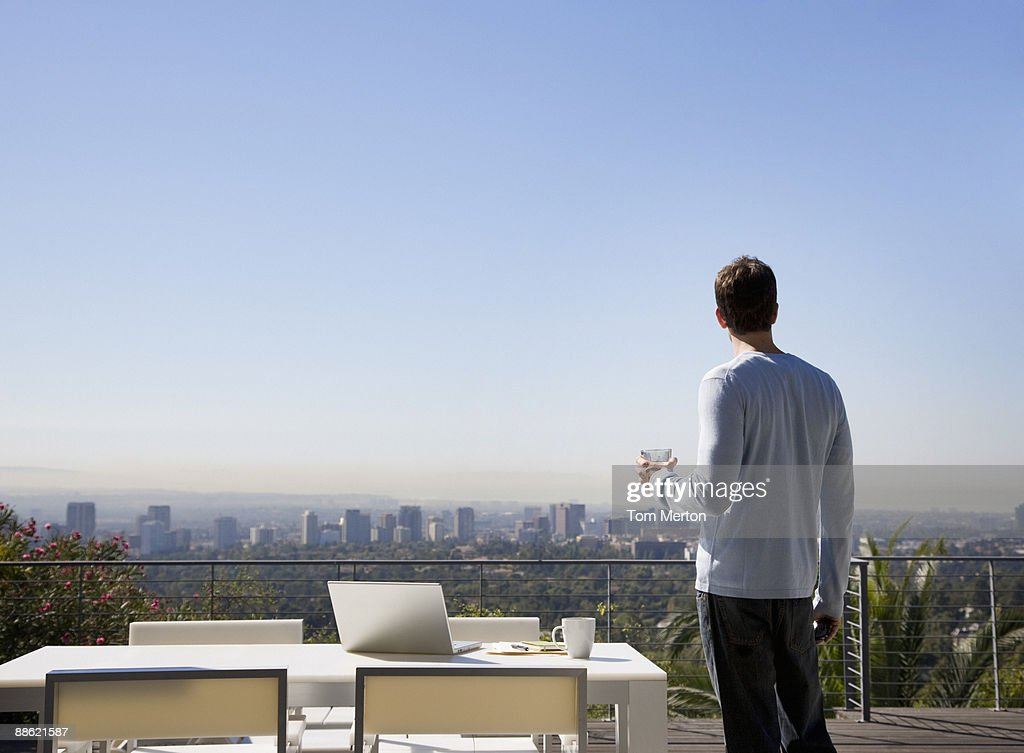Man using laptop on balcony overlooking city stock photo for Balcony overlooking city