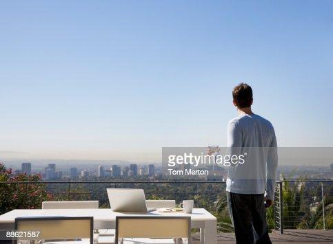 Homme à l'aide de portable sur balcon avec vue sur la ville : Photo