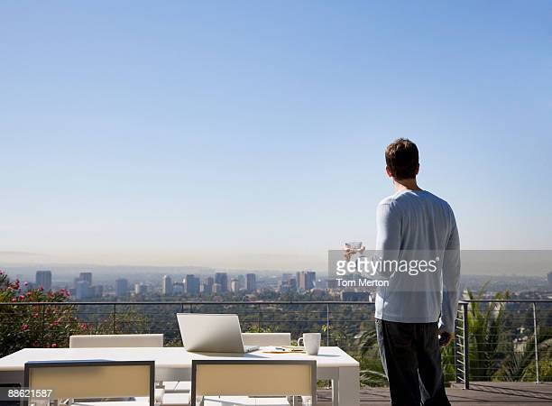 Uomo utilizzando un computer portatile sul balcone con vista sulla città