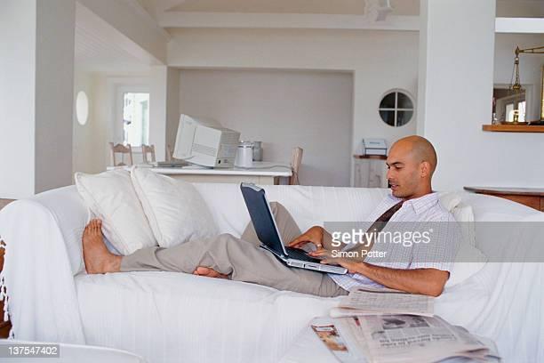 Uomo utilizzando un computer portatile sul divano