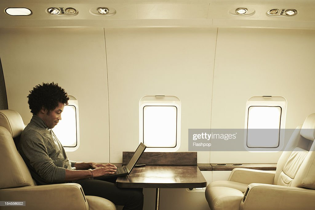 Man using laptop on private jet