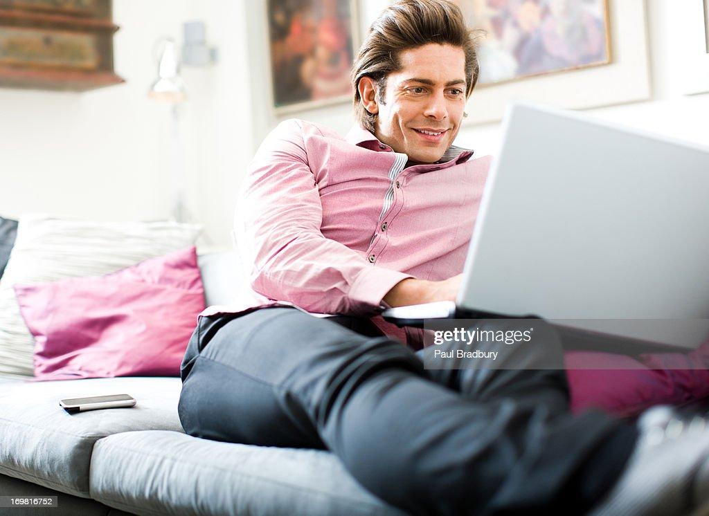 Man using laptop on sofa : Stock Photo