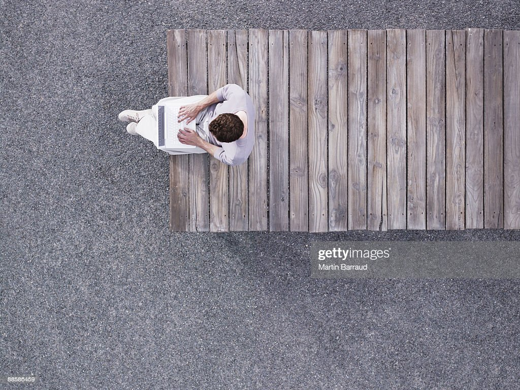 Man using laptop on wooden dock : Stock Photo