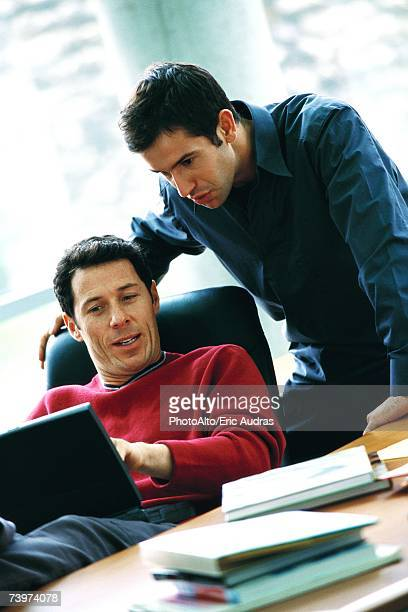 Man using laptop, talking to second man looking over shoulder