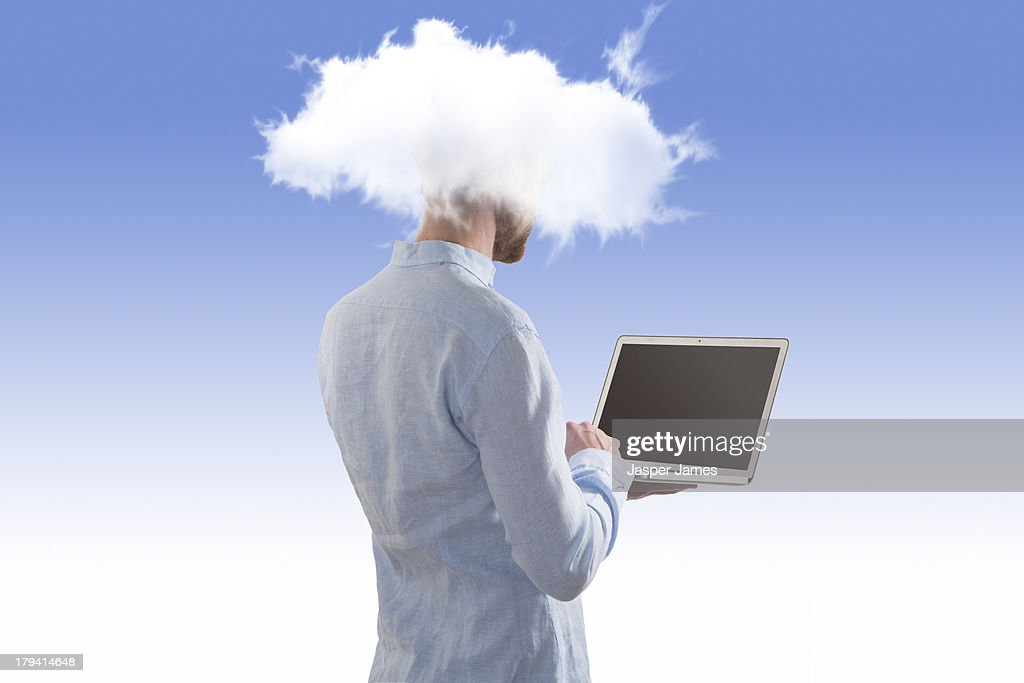 man using laptop with his head in the clouds : Stock Photo