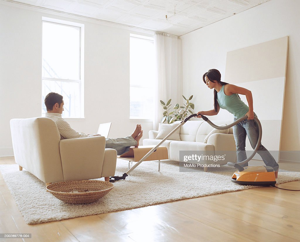 Man using laptop, young woman vacuuming living room rug : Stock Photo