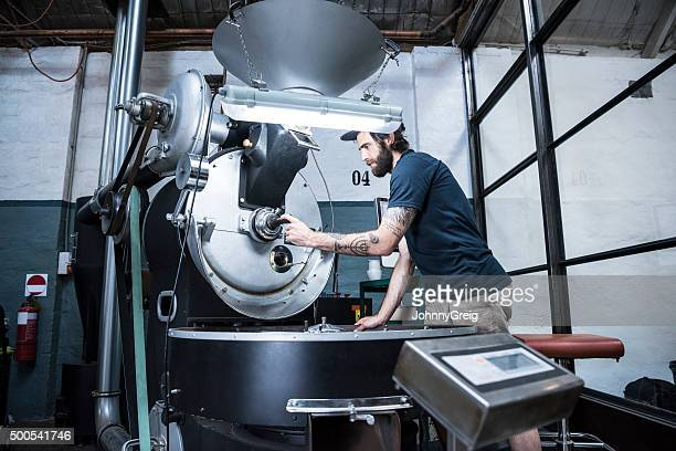 Man using machinery in coffee roasting warehouse