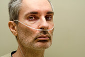 Portrait of middle aged man using medical oxygen.