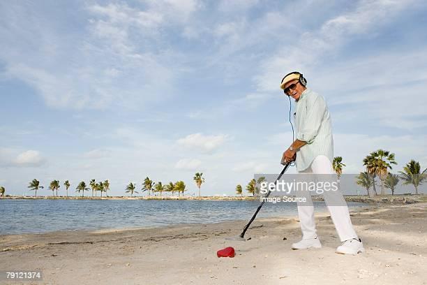 Homme avec Détecteur de métaux sur la plage