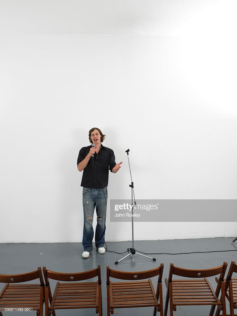 Man using microphone facing row of empty chairs : Stock Photo