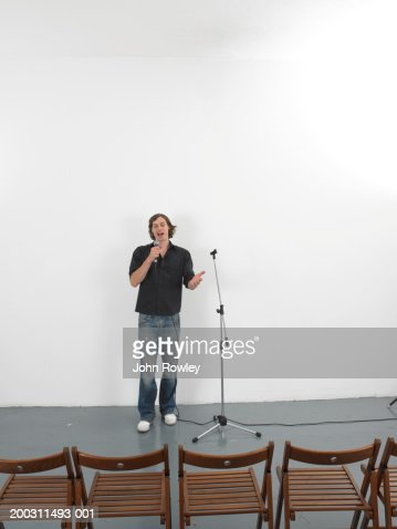 Man using microphone facing row of empty chairs