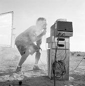 Man using microphone on movie set in desert (B&W)
