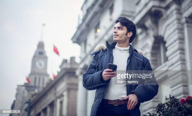 Man using mobile on sidewalk