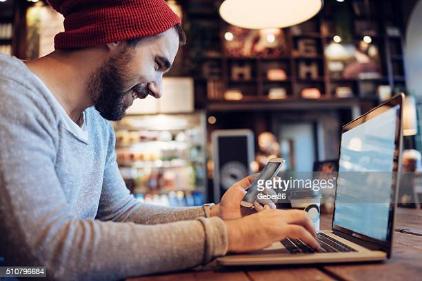 Man using mobile phone in cafe