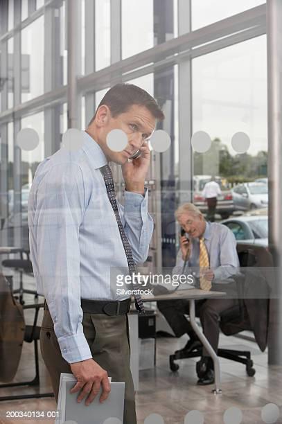Man using mobile phone in car showroom, salesman at desk in background
