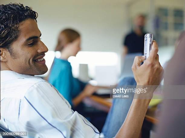 Man using mobile phone in office, close-up