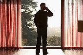 Man using mobile phone, looking through window