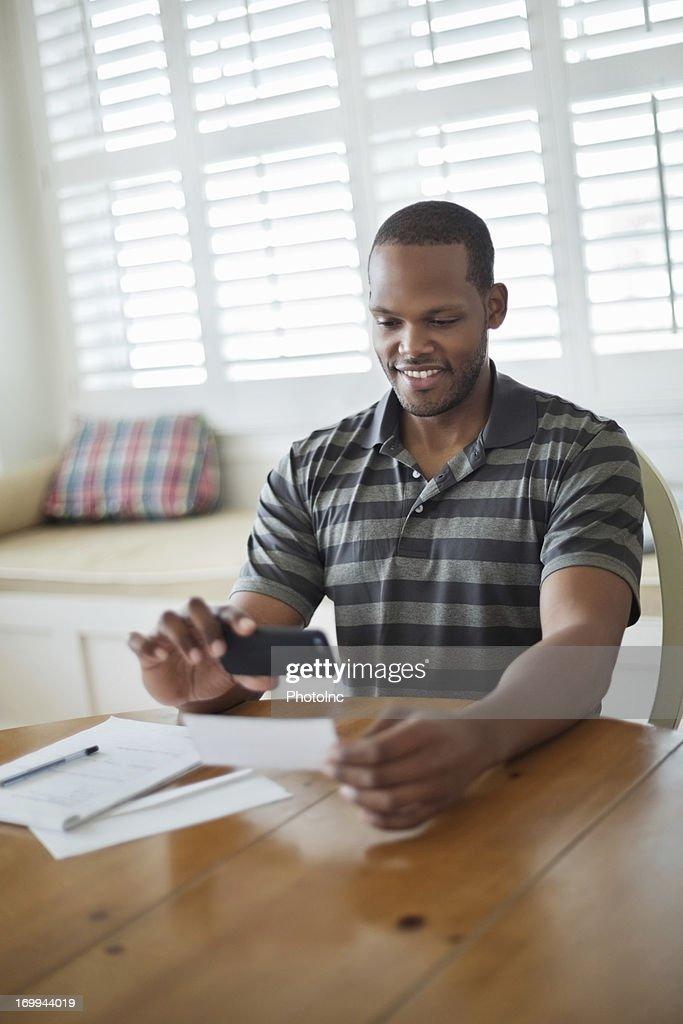 Man Using Mobile Phone To Deposit Bank Slip