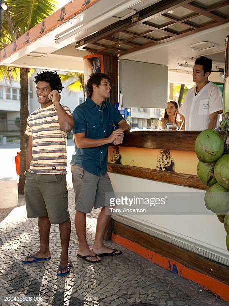 Man using mobile phone while other man is talking with bartender