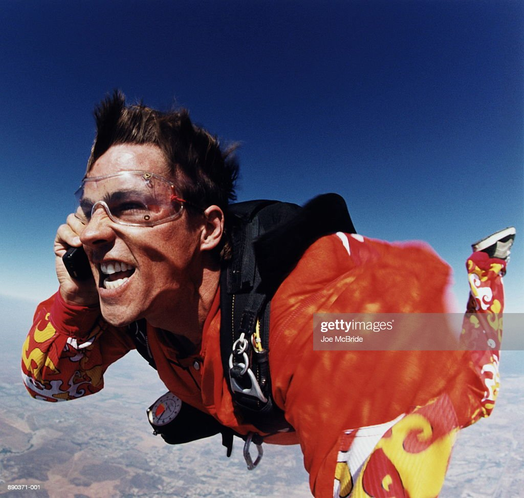 Man using mobile phone while sky diving : Stock Photo