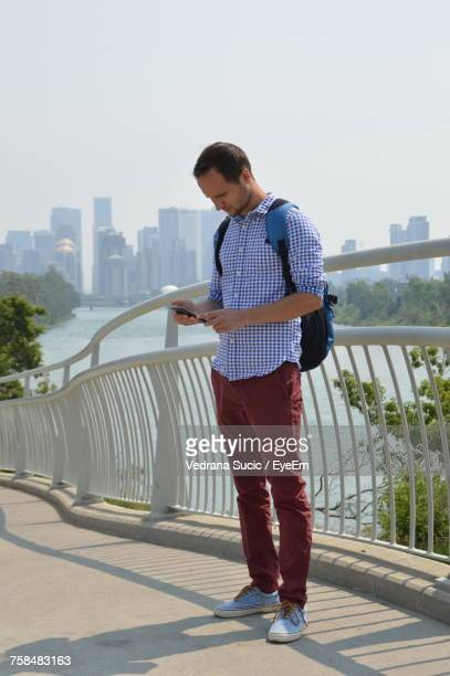 Man Using Mobile Phone While Standing On Bridge Against Railing