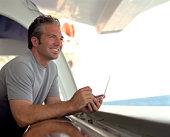 Man using PDA on ship