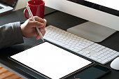 Man using pencil and blank screen tablet on workspace office table