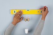 Man using pencil to draw line above spirit level and water pipes on wall