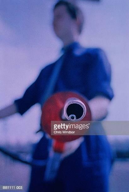 Man using petrol pump (focus on nozzle)