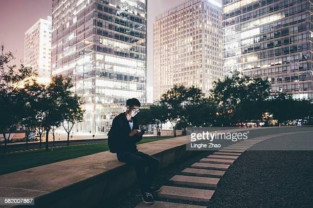 Man using phone at city night