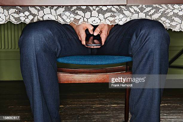Man using phone under table