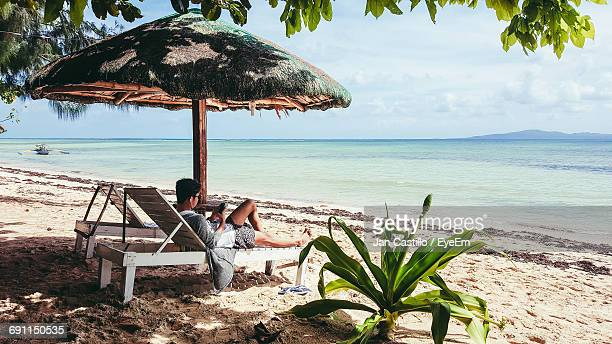 Man Using Phone While Resting On Lounge Chair At Beach Against Sky