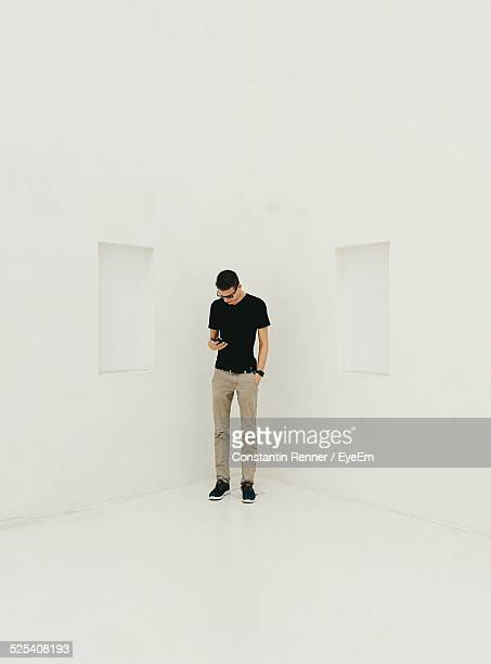 Man Using Phone While Standing In Corner Of White Room