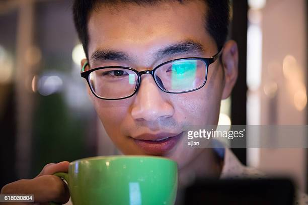 man using phone,drinking a cup of coffee