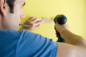 Man using power drill, biting screws in mouth