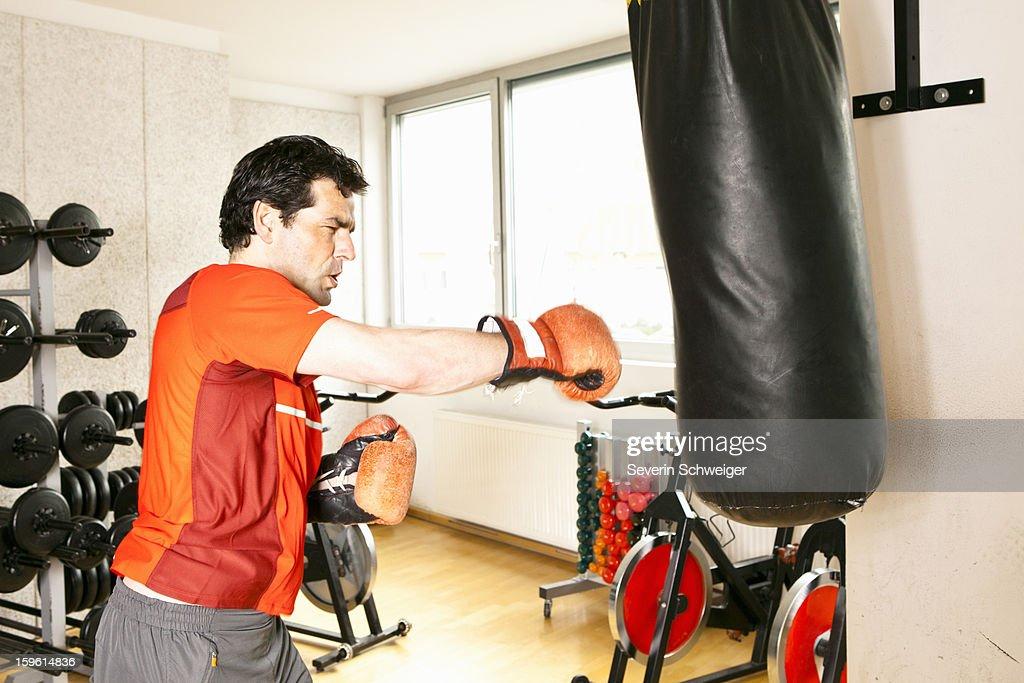 Man using punching bag at gym : Stock Photo