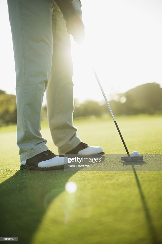Man using putter to play golf : Stock Photo