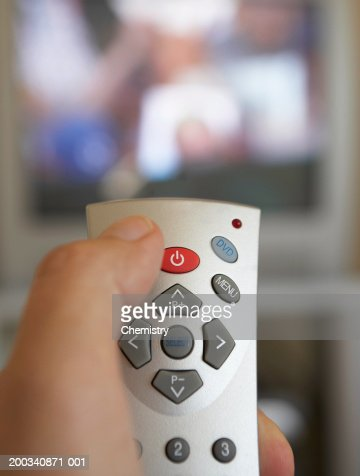 Man using remote control, close-up (focus on remote) : Stock Photo