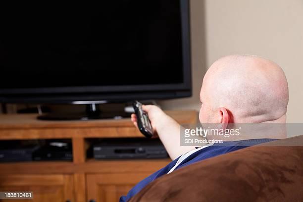 Homem com isolado enquanto assiste a programas de televisão