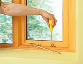 Man using screwdriver to install brass window stay on frame